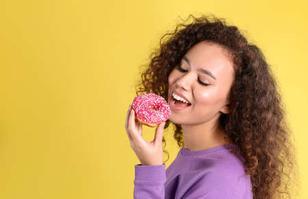 Beautiful African-American woman with donut on yellow background