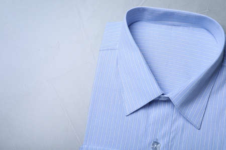 Stylish light blue shirt on grey background, top view with space for text. Dry-cleaning service