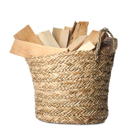 Wicker basket with cut firewood isolated on white Stockfoto