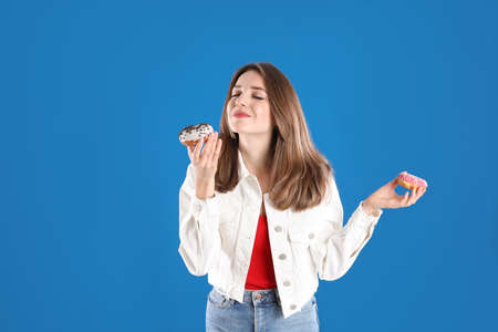 Beautiful young woman with donuts on blue background