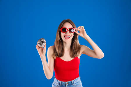 Beautiful young woman wearing sunglasses with donut on blue background