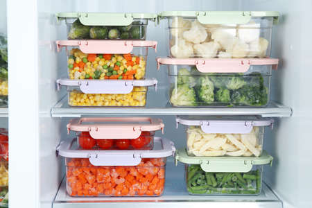 Containers with different frozen vegetables in refrigerator Banque d'images