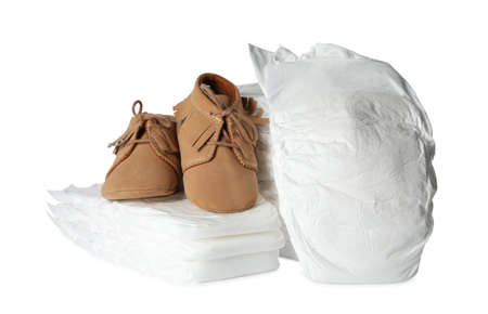 Disposable diapers and child's shoes on white background