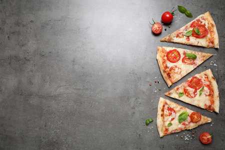 Slices of delicious pizza Margherita on grey table, flat lay. Space for text