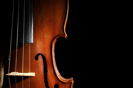 Classic violin on black background, closeup. Space for text