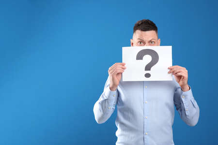 Emotional man holding paper with question mark on blue background. Space for text