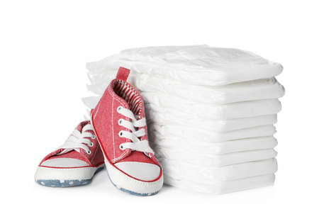 Stack of disposable diapers and child's shoes on white background Banque d'images