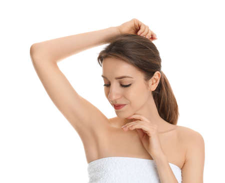 Young woman showing armpit with smooth clean skin on white background