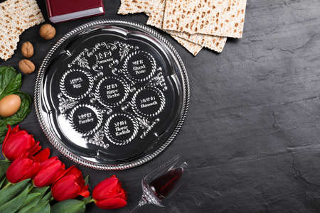 Flat lay composition with Passover Seder plate (keara) on black table, space for text. Pesah celebration