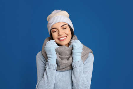 Young woman wearing warm sweater, gloves, scarf and hat on blue background. Winter season