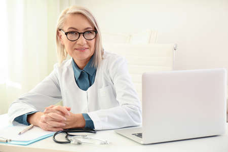 Portrait of mature female doctor in white coat at workplace