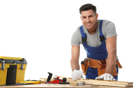 Handsome carpenter working with timber at wooden table on white background
