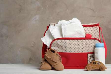 Bag with diapers and baby accessories on white wooden table. Space for text