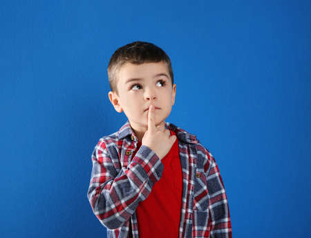 Thoughtful little boy in casual outfit on blue background 版權商用圖片 - 142674478