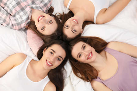 Beautiful young ladies on bed at pamper party, above view. Womans Day