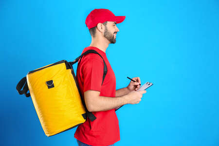 Courier with thermo bag and clipboard on light blue background, space for text. Food delivery service 版權商用圖片