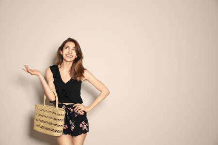 Young woman wearing floral print shorts with straw bag on beige background. Space for text 版權商用圖片 - 142674648