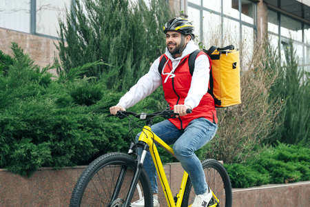 Courier with thermo bag riding bicycle outdoors. Food delivery service