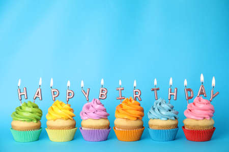 Birthday cupcakes with burning candles on blue background. Space for text