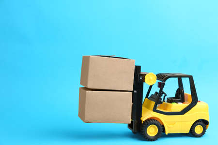 Forklift model and carton boxes on light blue background. Courier service