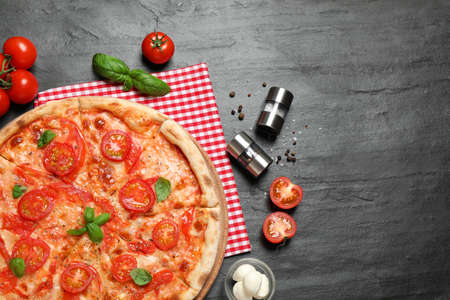 Delicious pizza Margherita and ingredients on dark grey table, flat lay 版權商用圖片