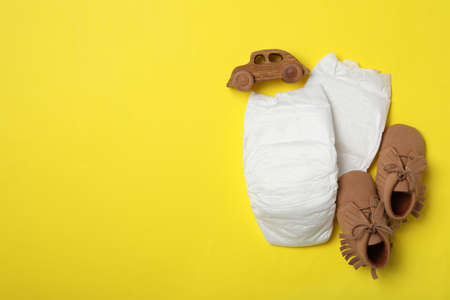 Diapers, toy car and child's shoes on yellow background, flat lay. Space for text Banque d'images