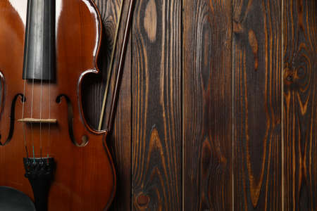 Classic violin and bow on wooden background, top view. Space for text