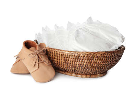 Wicker bowl with disposable diapers and child's shoes on white background Banque d'images - 142646539