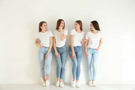 Beautiful young ladies in jeans and white t-shirts near light wall indoors. Woman's Day