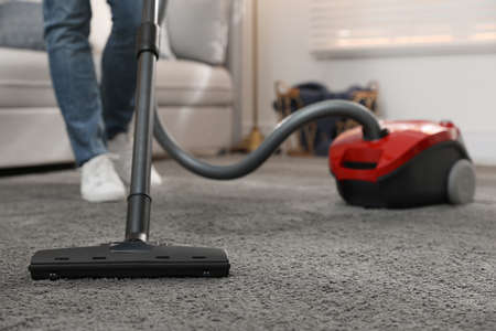 Young man using vacuum cleaner at home, closeup