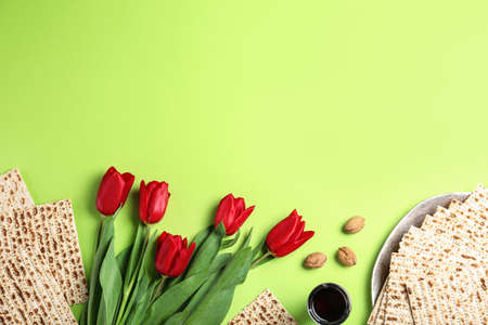 Flat lay composition with matzos on green background, space for text. Passover (Pesach) celebration