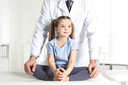 Professional orthopedist examining little girl in clinic