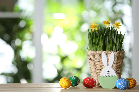 Easter bunny figure, dyed eggs and flowers on wooden table against blurred green background. Space for text