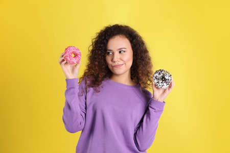 Beautiful African-American woman with donuts on yellow background