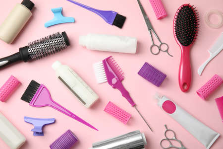 Professional tools for hair dyeing on pink background, flat lay