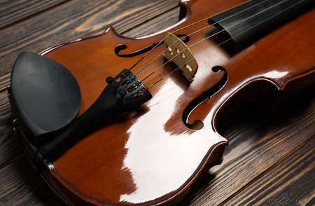 Classic violin on wooden background, closeup view Imagens