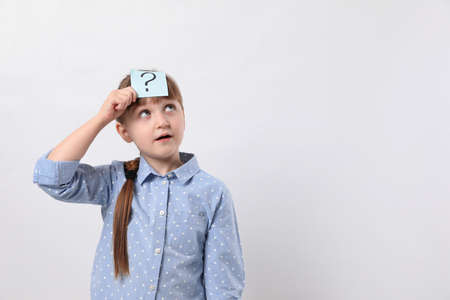 Emotional girl with question mark sticker on forehead against white background. Space for text