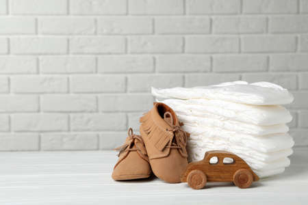 Baby diapers, toy car and child's shoes on wooden table against white brick wall. Space for text