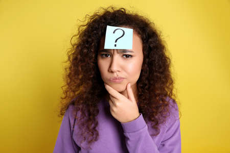 Emotional African-American woman with question mark sticker on forehead against yellow background