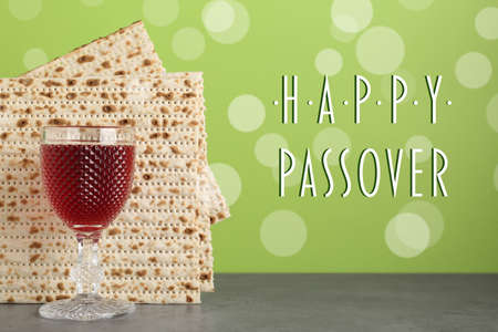 Passover matzos and glass of wine on grey table. Pesach celebration