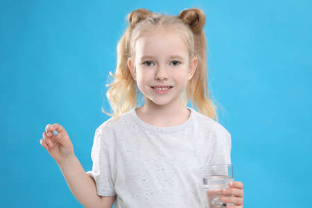 Little girl with vitamin pill and glass of water on blue background