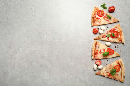 Slices of delicious pizza Margherita on light grey table, flat lay. Space for text