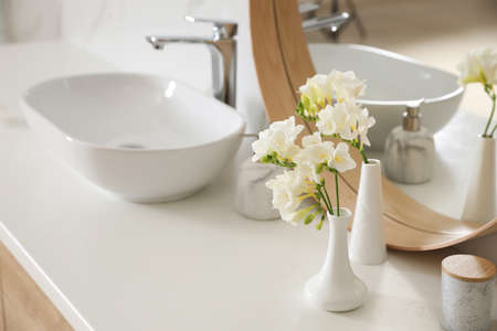 Beautiful white freesia flowers on countertop in bathroom, space for text