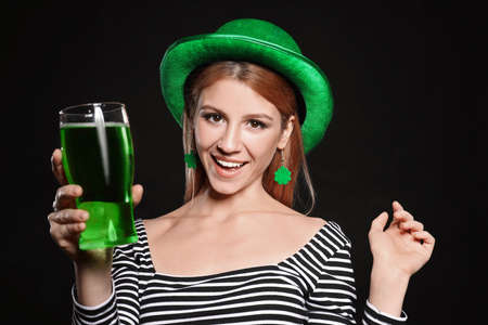 Young woman with green beer on black background. St. Patricks Day celebration