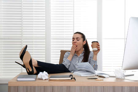 Lazy employee yawning at table in office