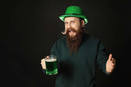 Bearded man with green beer on black background. St. Patrick's Day celebration Zdjęcie Seryjne - 143206947