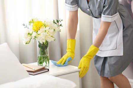 Young chambermaid wiping dust from nightstand in bedroom, closeup