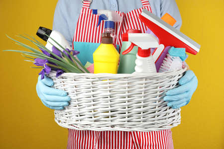 Woman holding basket with spring flowers and cleaning supplies on yellow background, closeup