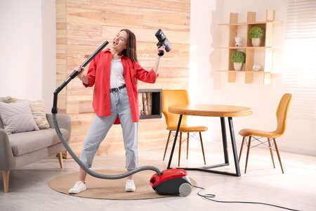 Young woman having fun while vacuuming at home Stock Photo
