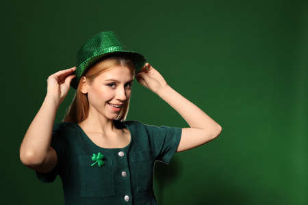 Young woman in green outfit on color background. St. Patricks Day celebration